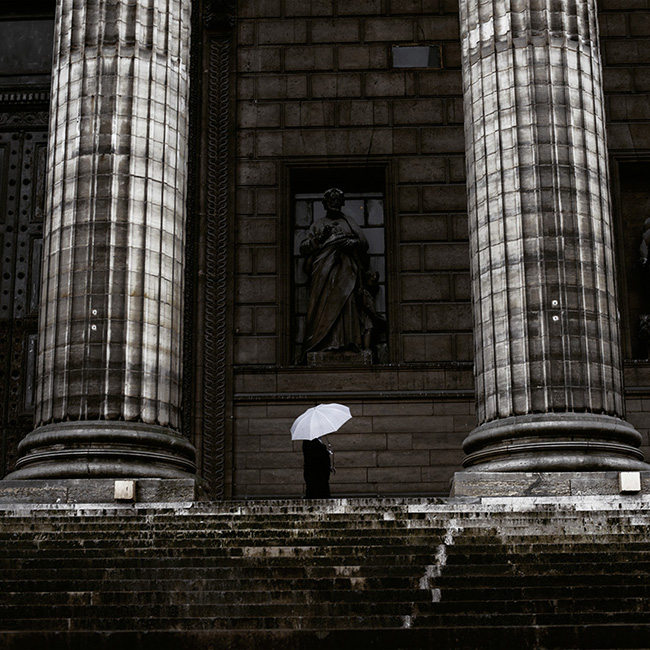In Paris, a man protects himself form the rain at La Madeleine.À Paris, un homme se protège de la pluie à La Madeleine.