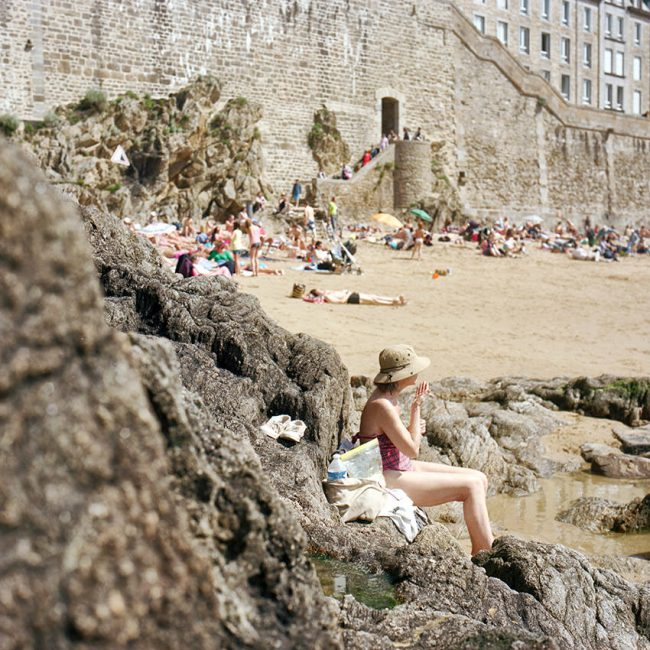 A tourist on the beach in Saint-Malo, Brittany