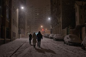 In Paris, three people are walking Corvisart's street under the snow by night.