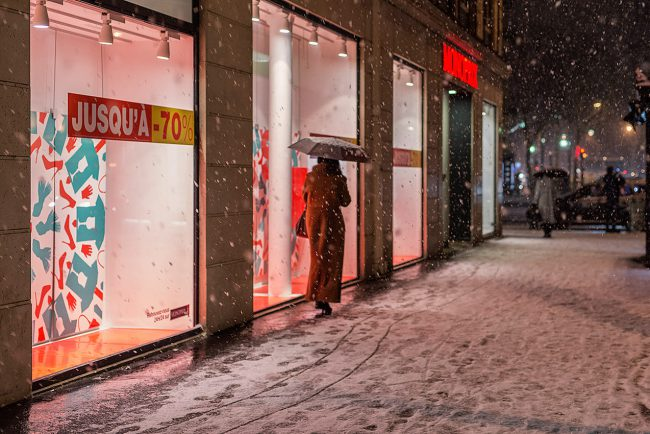 In Paris, a woman takes shelter from the snow under her umbrella at Boulevard Haussmann at night.