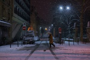 In Paris and at night, a man crosses snowy Corvisart Street with his umbrella.