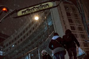 People are going out of the Parisian metro in the snow, at night.