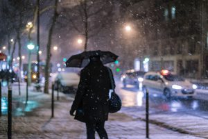 In the Parisian night, a man faces with his umbrella the snowstorm at Boulevard Haussmann.
