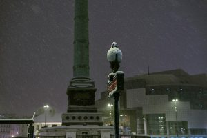 In Paris, by night, the snow is piling up on the panel of the metro station Bastille.
