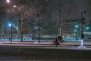 In a snow-covered Paris, a cyclist is waiting at a red light at Bastille by night.