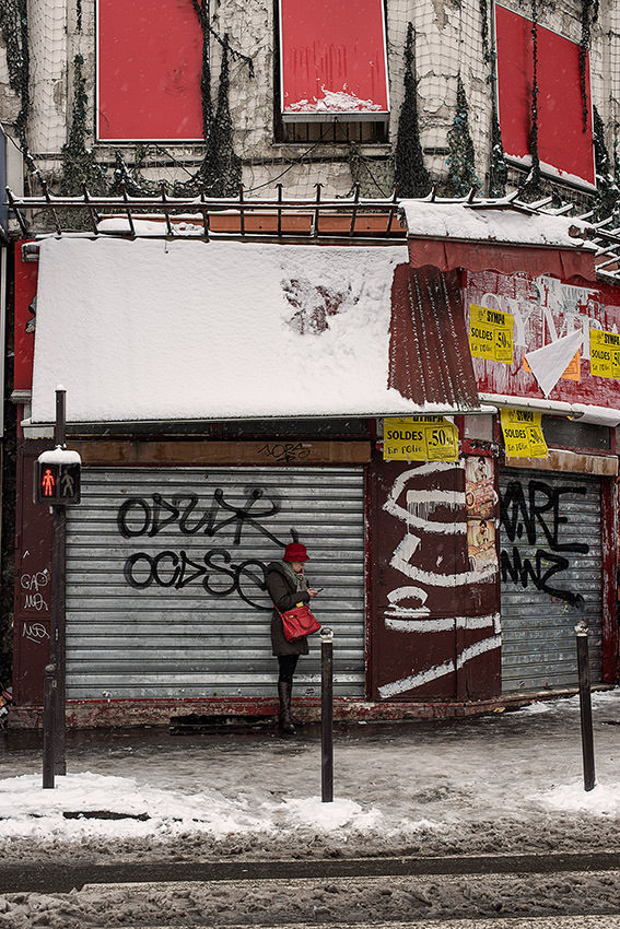 In a snowy Paris, a woman looks at her cell phone, Rochechouart boulevard.