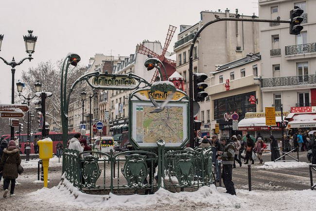 A pigeon flies over the metro station Blanche in Paris covered by snow.