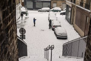 In Paris, a teenager takes a souvenir photo of his father in front of his snowy car.