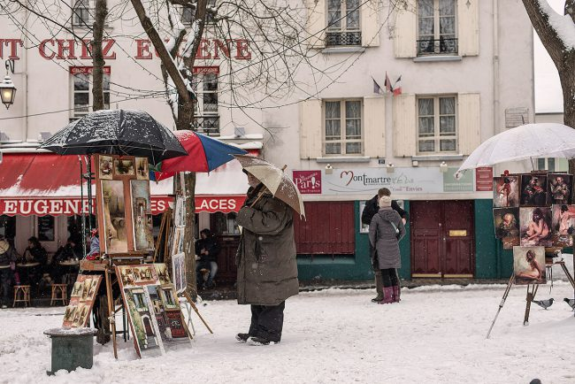 A painter protects himself from the snow, Place du Tertre in Paris .