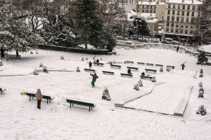 In Paris, a surfer is going down the slope of the snowy hill of Montmartre.