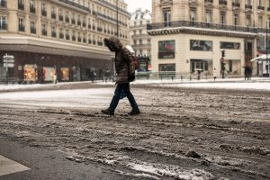 In Paris, a woman is crossing the totally snowy Haussmann Boulevard.