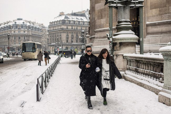 In Paris, a Japanese couple is walking on the snowy Opera square.