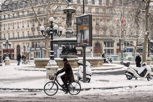 In Paris, a man on his bike rides on the snowy Avenue of the Opera.