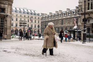 In Paris, an elderly woman is walking towards the metro on Place Colette.