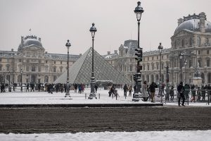 In Paris, the Louvre Museum and its pyramid are covered with snow.