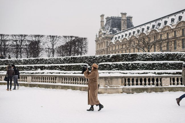 In Paris, a woman takes a picture of the Carrousel Arc de Triomphe in the snow.