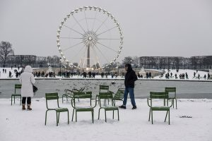 In Paris, a couple of tourists is standing around the large basin of the Tuileries gardens covered in snow.