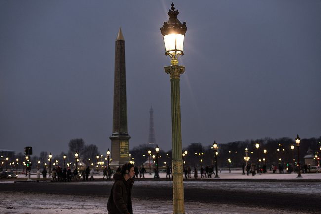In Paris, a young man is walking in the snow Concorde square at nightfall.