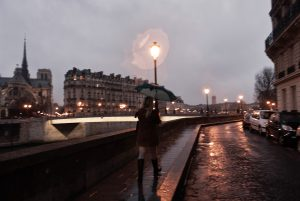 A woman walks down the quai d'Orléans, by a rainy evening in Paris.