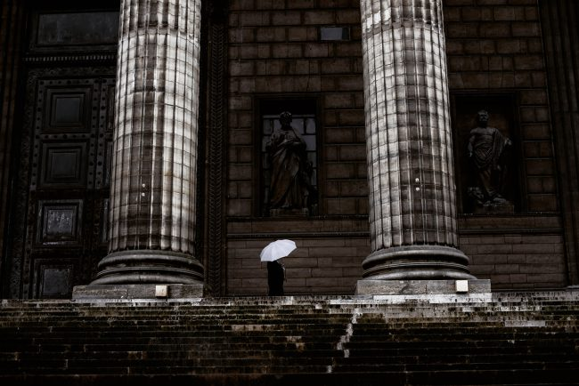 In Paris, a man protects himself form the rain at La Madeleine.