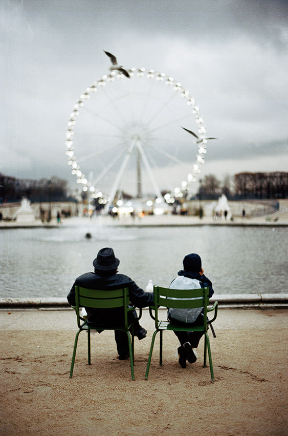 Father and son are sitted in front of the big wheel in Paris.