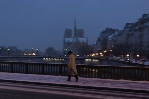 A man is walking Pont de Sully a snowy evening in Paris.