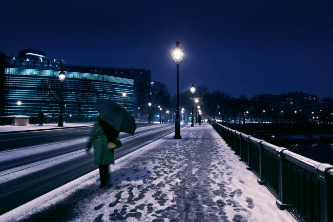 A woman is protecting herself from the snow on Sully's bridge in Paris.