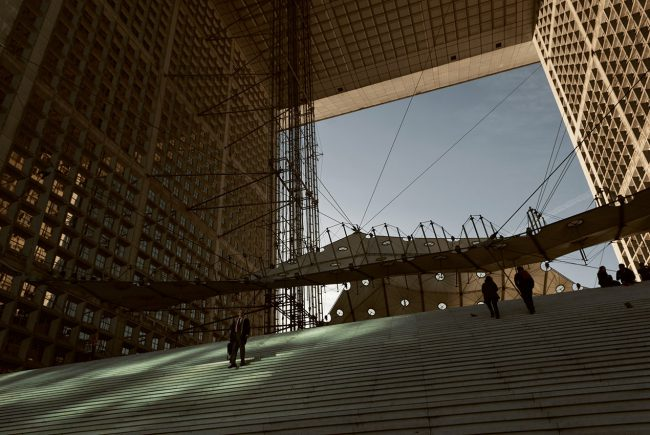 A man walks down the stairs of the Arche de la Défense.
