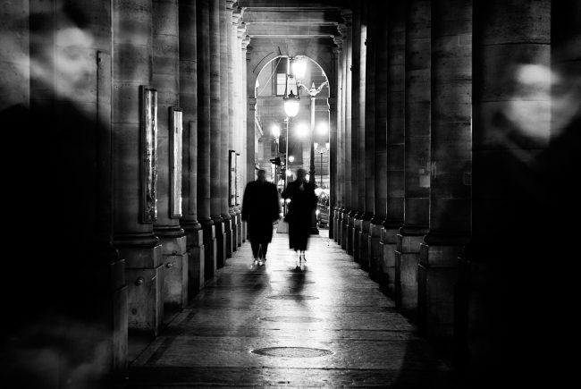 A couple is walking under the arcades of the Comédie Française in Paris.
