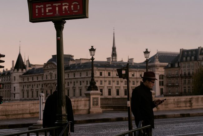 A Parisian is consulting his cell phone on the Pont Neuf in Paris.