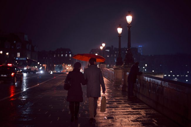 A couple crosses the Pont Neuf umbrella in hand.