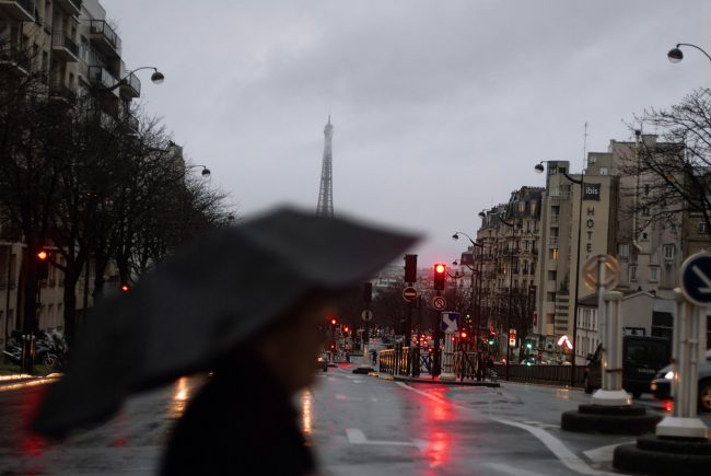 A man crosses the Boulevard Pasteur under the rain.