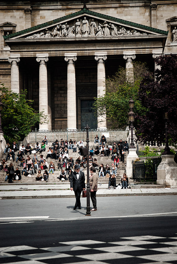 A man and a woman are talking in front of the St. Vincent de Paul parish in Paris.