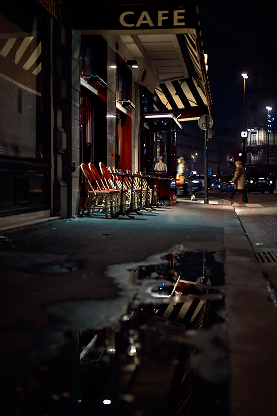 A deserted terrace of a cafe in the street of Châteaudun by night in Paris.