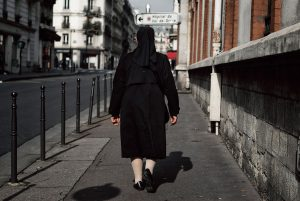 In Paris, a nun is walking down the street of La Glacière.
