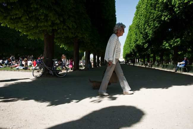 An elderly woman walks in the Luxembourg Gardens in Paris.