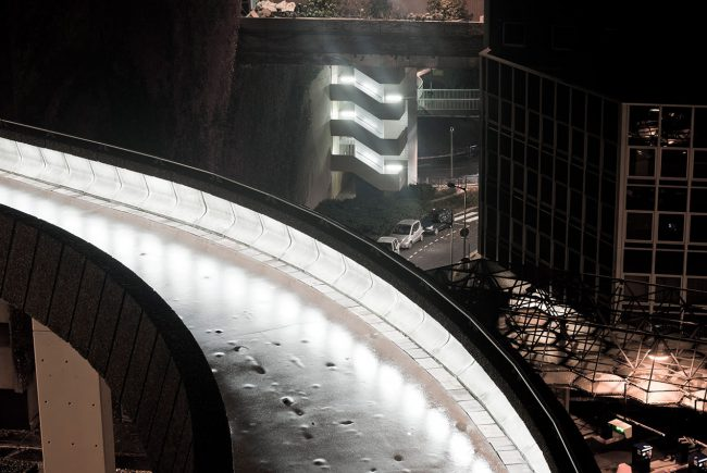 A night lit bridge leads to the Arche de la Défense in Puteaux.