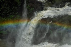 In Argentina, a rainbow is above the water Iguazu Falls.