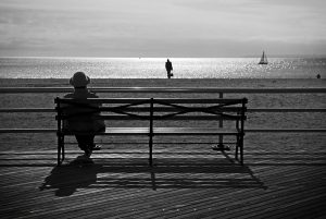 A woman sits on a bench on the boardwalk of Coney Island in NYC.