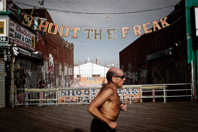 In NYC, A jogger runs along the Coney Island boardwalk.