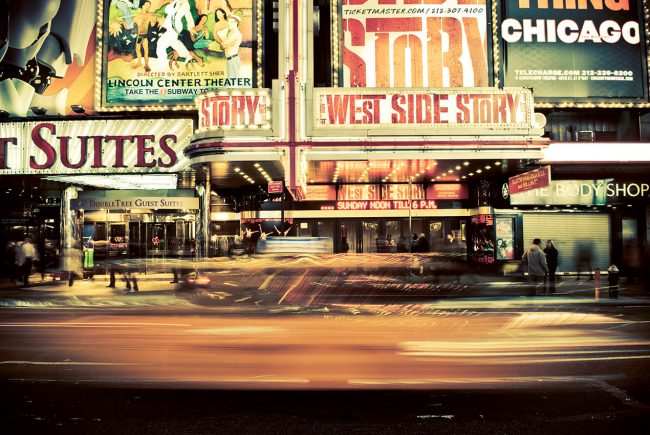 A taxi passes in Times Square in the Manhattan neighborhood of NYC.