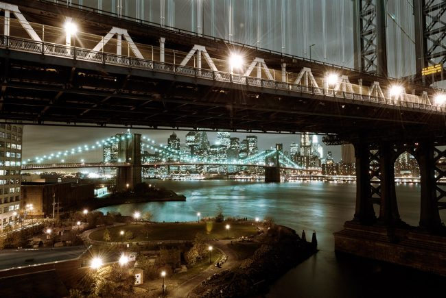 The Manhattan and Brooklyn bridges from the district of Dumbo at night in the city of NYC.