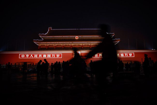 Cyclists are riding in front of the Forbidden City in Beijing by night.