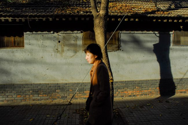 A woman is walking in the streets of the old part of Beijing.