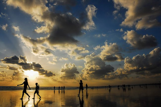 Tourists are walking on Kuta Beach in Bali.