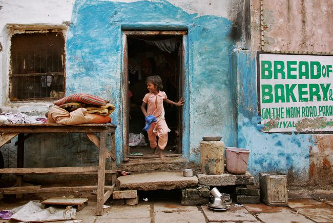 A small Indian girl is going out of her house in Varanasi, smiling.