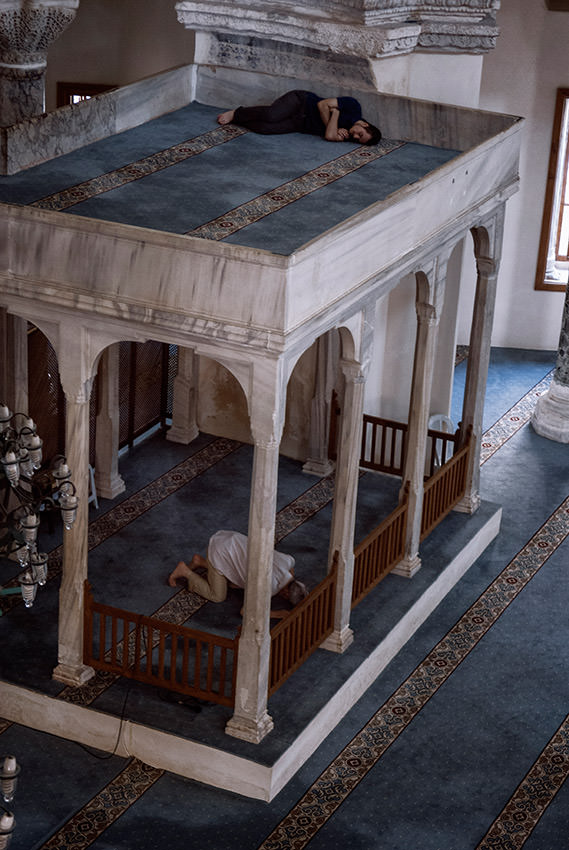 In a mosque of Istanbul, a man prays while another sleeps.