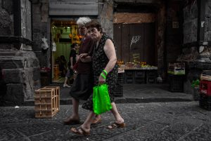 Two old women walk through the old streets of Naples in Italy.