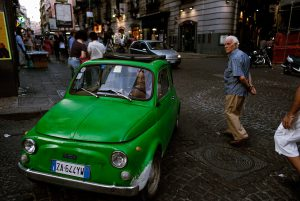 A man is driving a Fiat 500 in the streets of Naples.