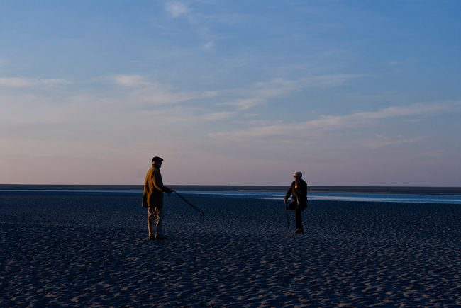 A couple is walking on a beach in Normandy.